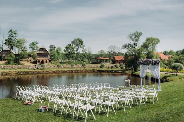 Decoratie van de huwelijksceremonie in de zomer in de buurt van het meer op het groene gras. prachtig ingerichte huwelijksceremonie.