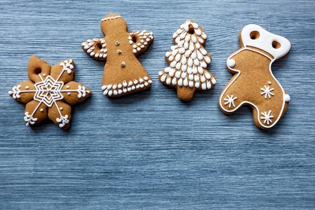 Decoratie van gemberkoekjes in de vorm van een sneeuwvlok, hert, kerstboom en een engel voor de kerstboom op een houten achtergrond