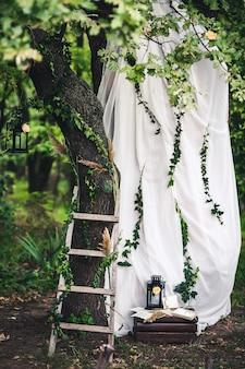 Decoratie voor de bruiloft zwarte lantaarns klimop twijgen riet trap witte stof bloemen op eikenhout
