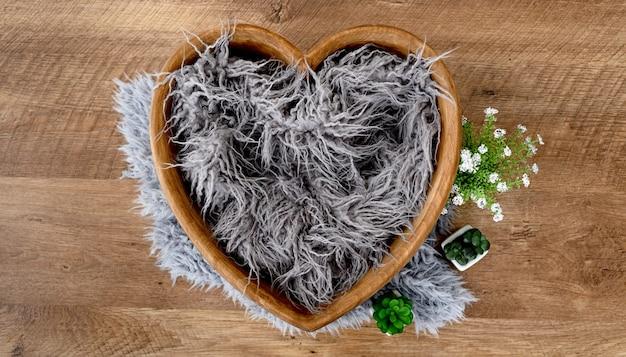 Decoratie voor newborn studio fotoshoot. klein houten hartbed met bont en bloemen voor babyfoto's van baby's