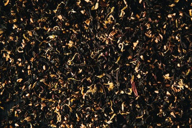 Decoratief full-frame beeld van droge groene en zwarte thee en fruit- en bloemtoevoegingen