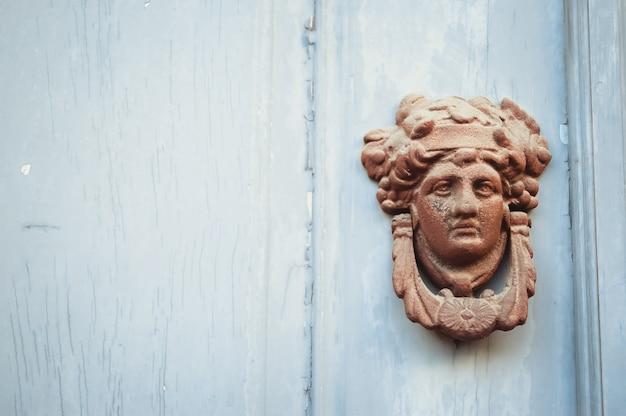 Decoratief gezicht deurknop gemaakt van metaal op een blauwe houten deur