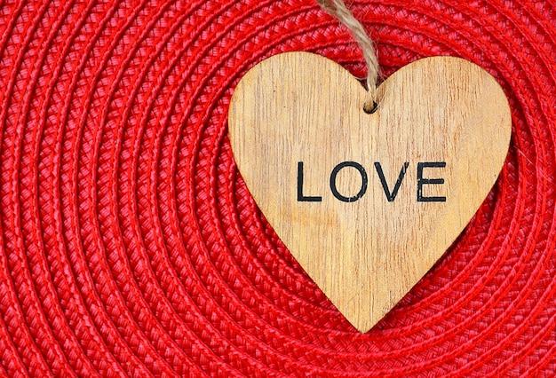Decoratief hart met tekst love op een rood textieloppervlak