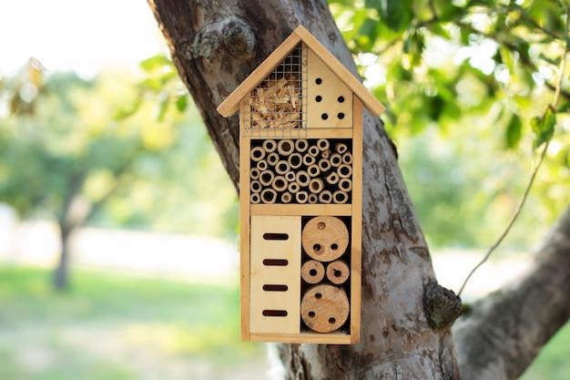Decoratief insectenhuis in tuin. bijenhuis voor winterslaap, ecologisch tuinieren.