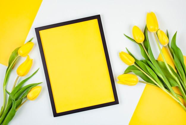 Decoratief leeg frame met exemplaarruimte en boeket van tulpen