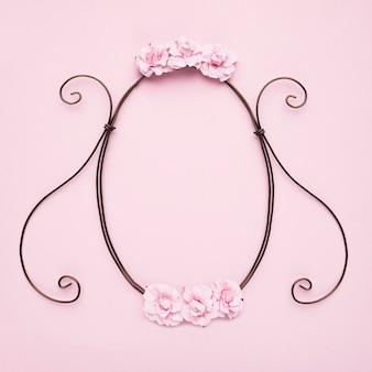 Decoratief leeg kader met rozen op roze muur