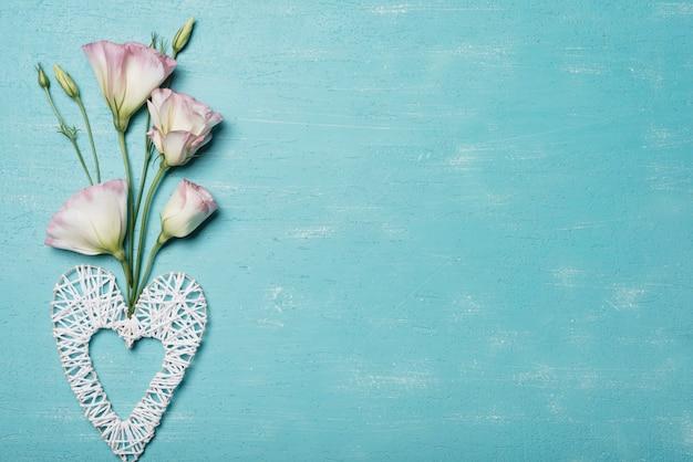 Decoratief met de hand gemaakt hart met eustomabloemen tegen blauwe geweven achtergrond