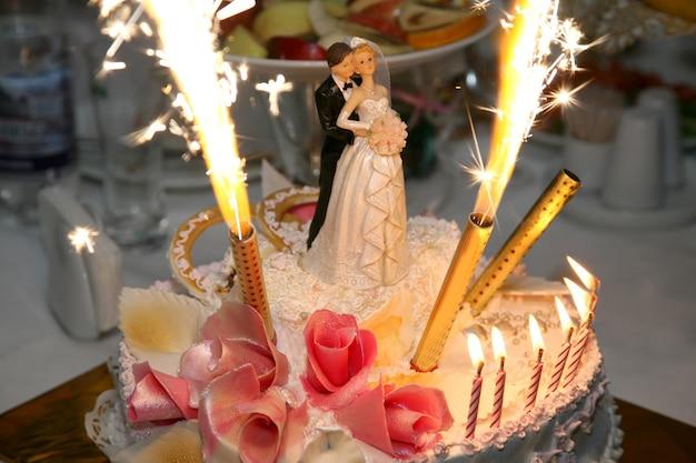 Decoratief paar pasgetrouwden met kaarsen op een bruidstaart