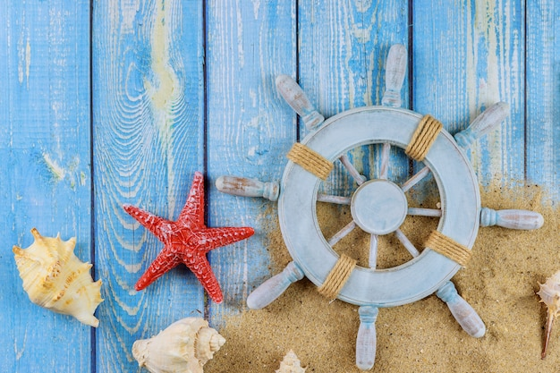 Decoratief stuur met zeester, schelpen op het zandstrand en houten planken