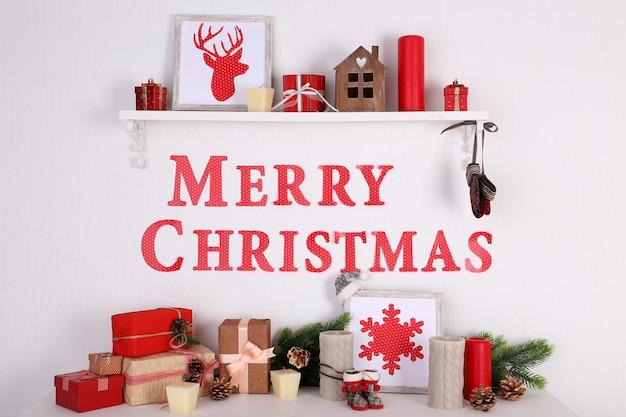 Decoraties met merry christmas-inscriptie op schoorsteenmantel op witte muurachtergrond