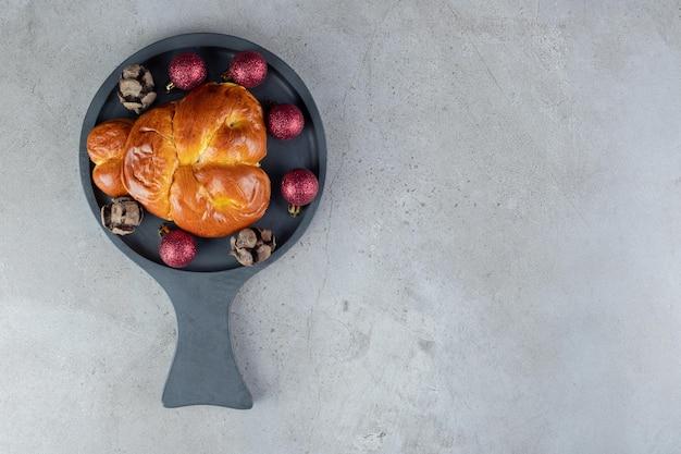 Decoraties rond een broodje op een schaal op marmeren tafel.