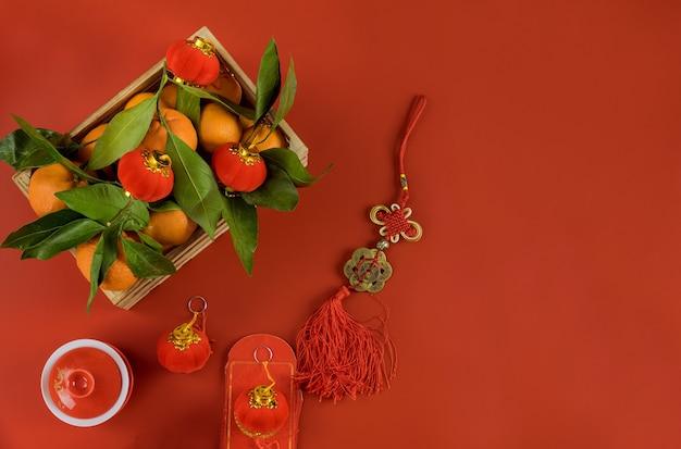 Decoraties van accessoires in chinees nieuwjaar ceremoniefestival in traditionele container mandarijn sinaasappelen op een rood