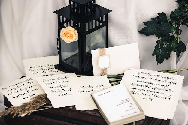 Decoraties voor de bruiloft: zwart metalen lantaarn, roos, klimop takje, stok, vintage papier met mooie tekst, envelop, doos, ansichtkaart.