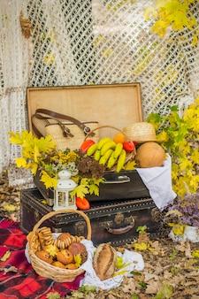 Decoraties voor herfstpicknick in bos. retro foto in de natuur. warme herfstdagen. nazomer. rustiek herfst stilleven. oogst of thanksgiving. herfst decor, feest. lantaarn, bananen, pompoen