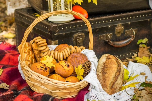 Decoraties voor herfstpicknick in bos. retro foto in de natuur. warme herfstdagen. nazomer. rustiek herfst stilleven. oogst of thanksgiving. herfst decor, feest. lantaarn, vintage koffers