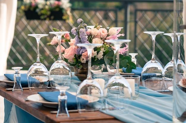 Decoratietafelopstelling, blauwe servetten, bloemen, buitenshuis, bruiloft of ander evenement