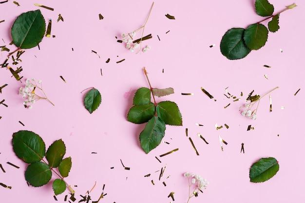 Decoratieve achtergrond van heldere confetti decoratie, gypsophila bloemen en groene bladeren op een roze achtergrond.
