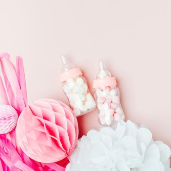 Decoratieve babymelkflessen met snoep en papieren versieringen voor een babyshowerfeestje. platliggend, bovenaanzicht