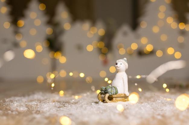 Decoratieve beeldjes met kerstthema. het beeldje van een ijsbeer zit op een houten slee, in een gebreide muts en sokken.