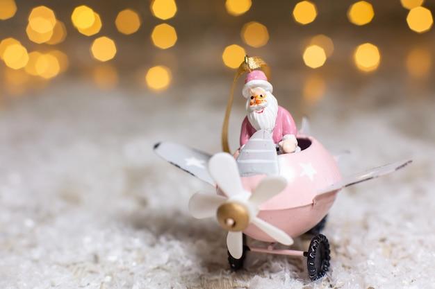 Decoratieve beeldjes van een kerstthema. santa claus in een roze vliegtuig met een propeller.