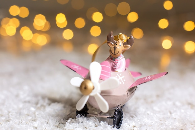 Decoratieve beeldjes van een kerstthema. santa's deer in een roze vliegtuig met een propeller.