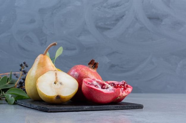 Decoratieve bladeren met gesneden en hele peren, granaatappels en mandarijnen op een zwart bord op marmeren achtergrond.