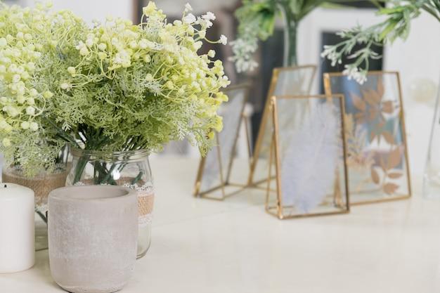 Decoratieve bloemen kaarsen en gedroogde planten in frame op kaptafel