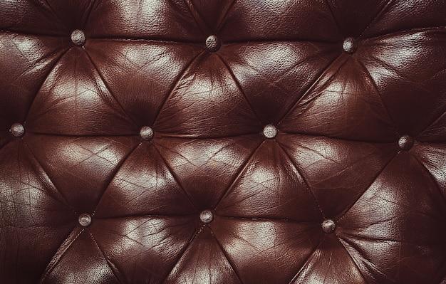 Decoratieve bruine achtergrond van echt leer. decoratieve achtergrond van echt leder capitone textuur