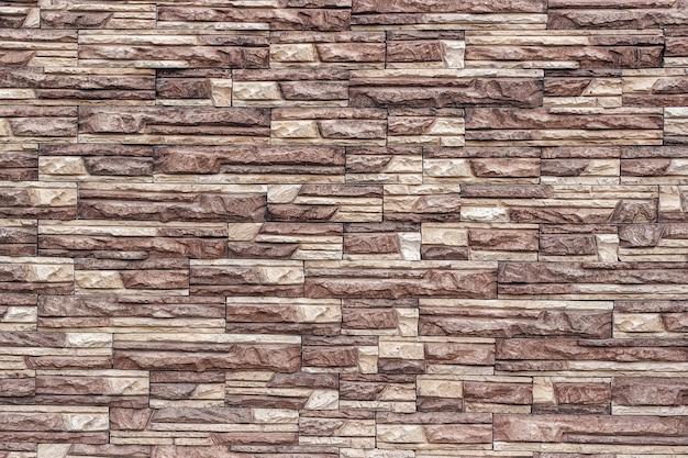 Decoratieve bruine muur van kunstmatige gescheurde steen als achtergrond of textuur.