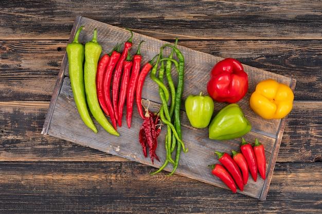 Decoratieve compositie met chili en paprika's bovenaanzicht op een houten snijplank op hout