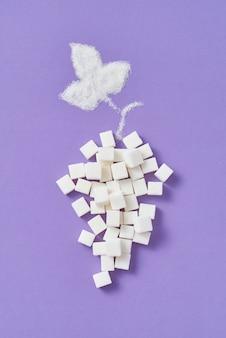 Decoratieve compositie van druivenfruit handgemaakt van verschillende soorten zoete suiker geraffineerde blokjes en blad van kristalsuiker op een lavendelmuur, kopie ruimte. plat leggen.