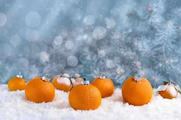 Decoratieve compositie van kerstversiering gemaakt van mandarijnen op witte sneeuw. abstracte blauwe achtergrond met lichten en sneeuw