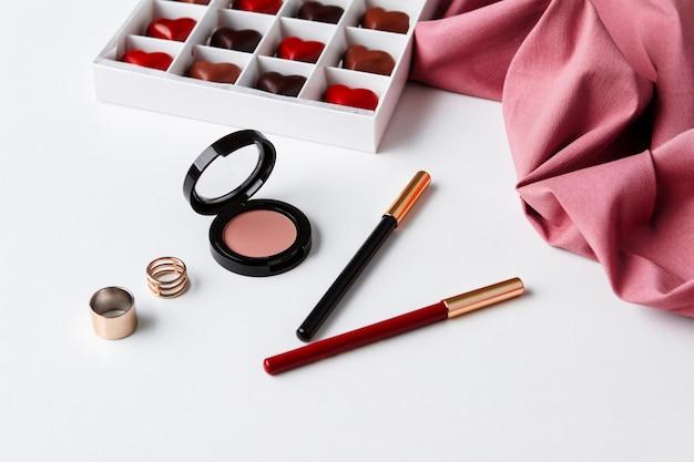 Decoratieve cosmetica accessoires en chocolade op een wit oppervlak