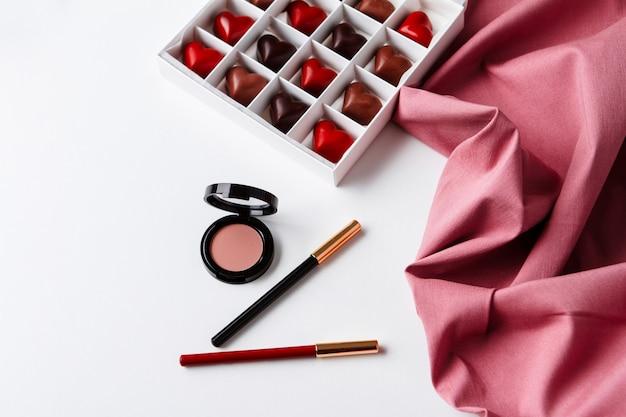 Decoratieve cosmetica en chocolade over wit oppervlak