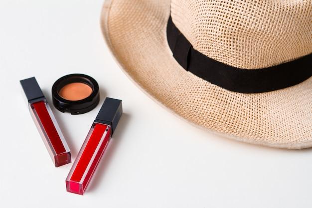 Decoratieve cosmetica en hoed over wit oppervlak