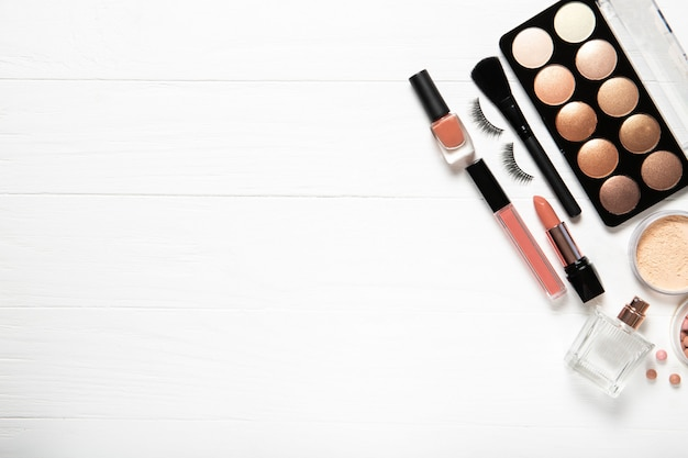 Decoratieve cosmetica en make-up borstels op een witte muur, bovenaanzicht. plaats voor tekst