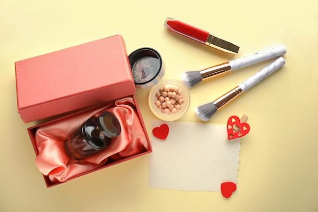 Decoratieve cosmetica met parfum en blanco kaart op lichte achtergrond