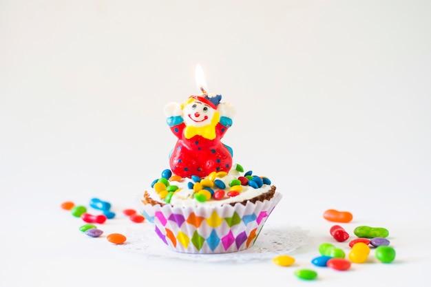 Decoratieve cup cake met verlichte clown kaars op witte achtergrond