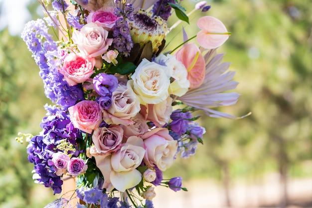Decoratieve decoratie van de huwelijksboog met verse bloemen. het houden van een huwelijksceremonie in de open lucht. decoratiedetails