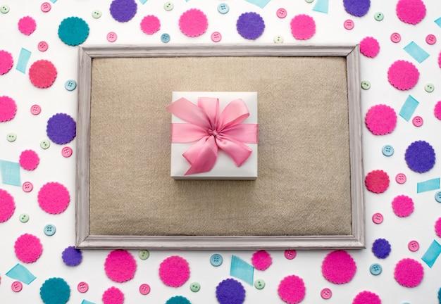 Decoratieve feestelijke achtergrond met gekleurde confetti doos met cadeau