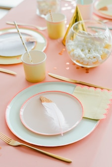 Decoratieve feestelijke tafel instelling voor kinderfeestje diner met textielroze tafelkleed, papier kleurrijke borden. gelukkige verjaardag voor meisje of baby showerdecoratie