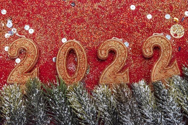 Decoratieve figuren van het nieuwe jaar en kerst gouden kaarsen op een rode achtergrond frame van sparren ...