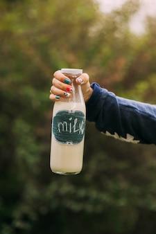 Decoratieve fles melk in de hand