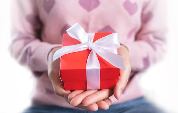 Decoratieve geschenkdoos met wit striklint. cadeau in de handen van een vrouw. meestal gebruikt voor verjaardagen, jubileumcadeaus, belangrijke dagen, kerstmis, nieuwjaar, concept.