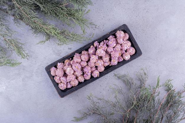Decoratieve groenblijvende takken en een dienblad met snoep gecoate popcorn op marmeren achtergrond. hoge kwaliteit foto