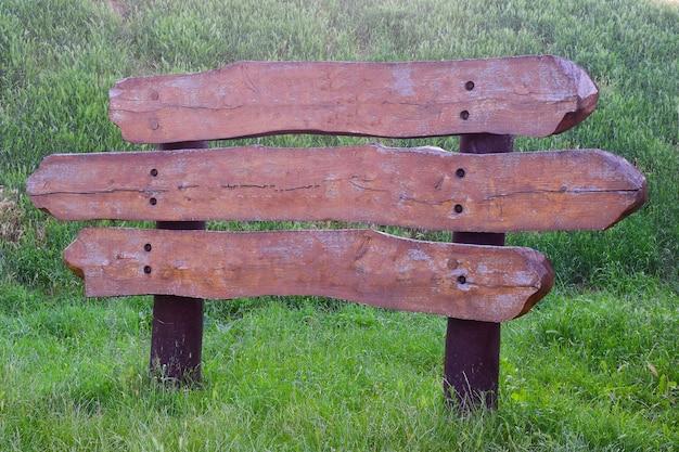 Decoratieve grote wegwijzer van drie horizontale borden met lege ruimte voor inscripties op elk van hen tegen een achtergrond van groen gras