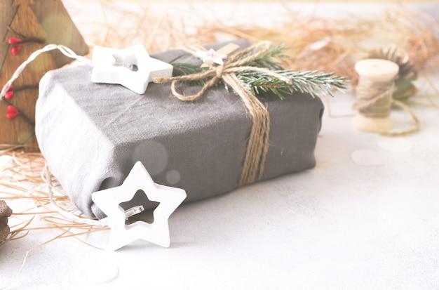 Decoratieve houten kerstboom en ster, kegel en stof verpakte geschenken, op een lichte achtergrond. geen afvalconcept