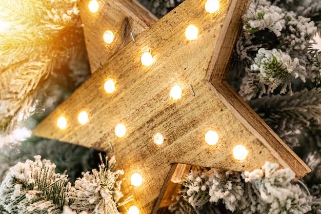 Decoratieve houten ster met lampen die op pijnboomtakken hangen