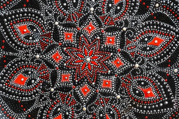 Decoratieve keramische plaat met rode en zilveren kleuren, geschilderde plaat op achtergrond, close-up, bovenaanzicht. decoratief porseleinen bord beschilderd met acrylverf, handwerk, stippenschildering