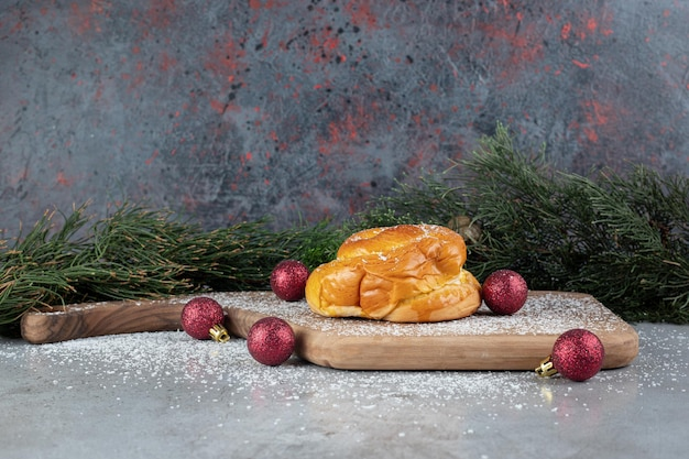 Decoratieve kerstbollen, dennentakken en een klein broodje op marmer